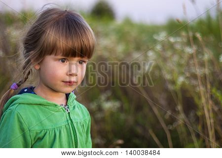 Cute little girl looking seriously ahead portrait
