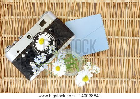 old retro camera with daisies and a card to wishes of the a top view / take pictures with a floral mood
