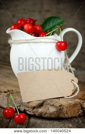 Ripe cherries in a white jar with brown paper tag selective focus
