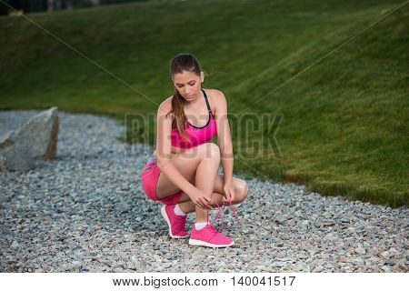 Running shoes - woman tying shoe laces. Female sport fitness runner getting ready for jogging outdoors on park path in late summer or fall.
