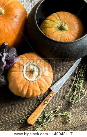 Pumpkin, Basil, thyme kitchen knife on a wooden Board