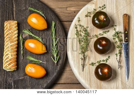 Yellow and black tomatoes on wooden Board