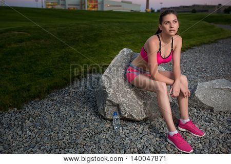 Young woman resting after running exercise. tired woman runner taking a rest after running hard on road