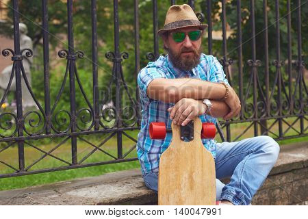 Hipster man sitting at the park with long board. Handsome men in sunglasses and hat posing outdoor.