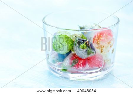 Fresh fruits and berry frozen in ice cubes on blue background. Fresh healthy summer cold eating blank space for text selective focus