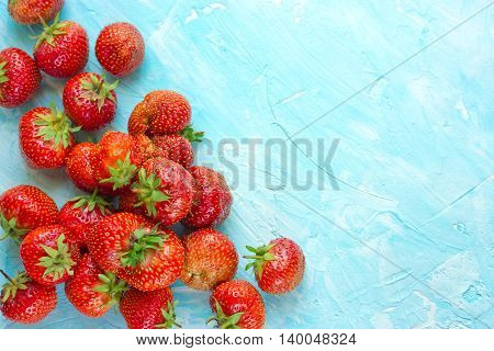 Ripe red strawberry on blue background blank space for text top view