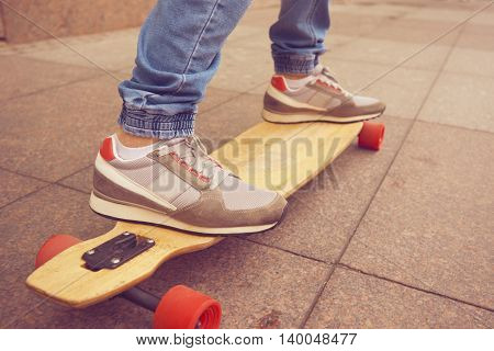 Close up shot longboarders legs in outdoors action