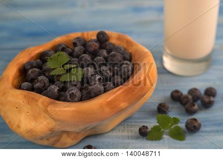 Close up of a wooden bowl full with blueberry