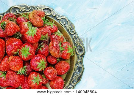 Ripe red strawberry on old vintage copper tray on blue background blank space for text top view
