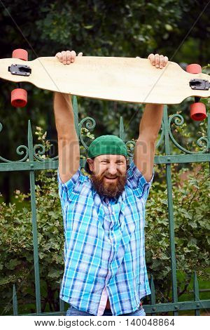 Cheerful hipster man posing with longboard and on fashionable green cap