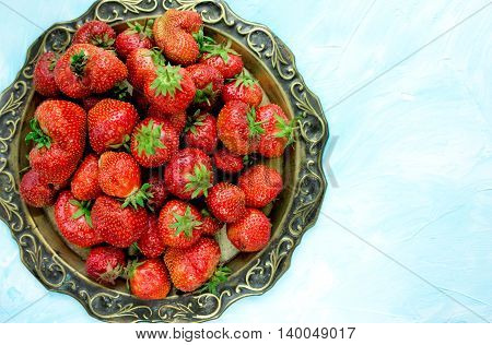 Ripe red strawberry on old vintage copper tray blank space for text top view