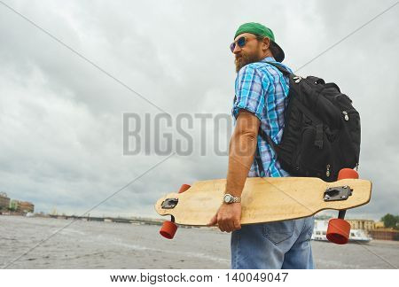 Handsome hipster guy stand with longboard over city river background