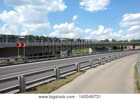 Cityscape with empty urban highway, overhead road and pedestrian way with fence in sunny summer day horizontal photo closeup