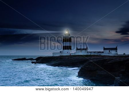Lighthouse beacon in a stormy night, Ireland