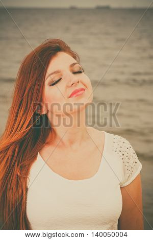 Holidays vacation travel and freedom concept. Attractive red haired girl closed eyes outdoor sky background. Young pretty woman relaxing on the sea coast.