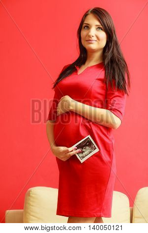 New life concept. Pregnancy motherhood and happiness. Tummy of pregnant woman wearing elegant red dress ultrasound scan in hand indoor