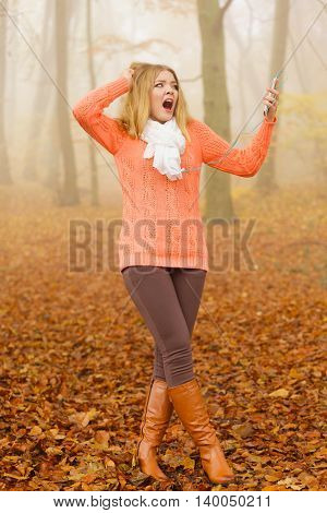 Young woman with earphones and smartphone listening to terrible music. Terrified scared girl in foggy fall autumn park. Bad music taste and technology concept.