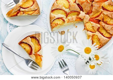 Classic peach pie on table with flower top view
