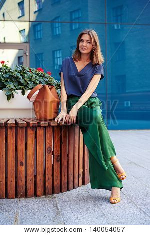 Young slim attractive woman in stylish elegant clothes is sitting on bench in downtown of the city