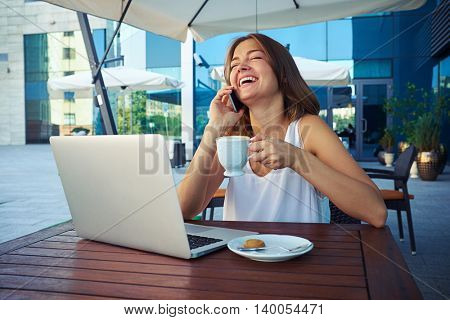 Attractive female is sitting outdoors on cafe open terrace with laptop and a cup of coffee and laughing while talking on the mobile phone
