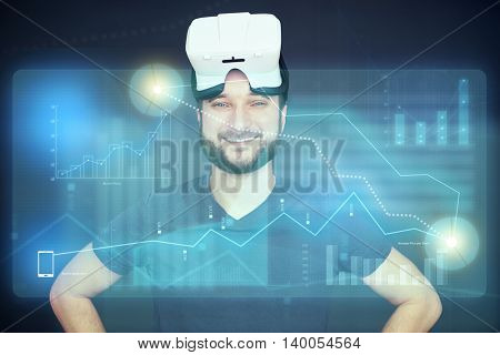 Portrait of young smiling bearded man wearing virtual reality glasses on his head with high tech interactive digital screen in front of him