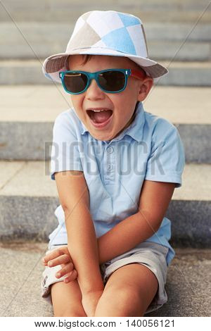 Close-up shot of cute small boy in sunglasses and hat sitting on stairs with excited face