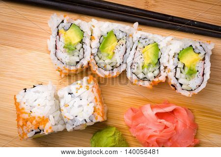 Sushi California rolls appetizer with rice avocado with chopsticks