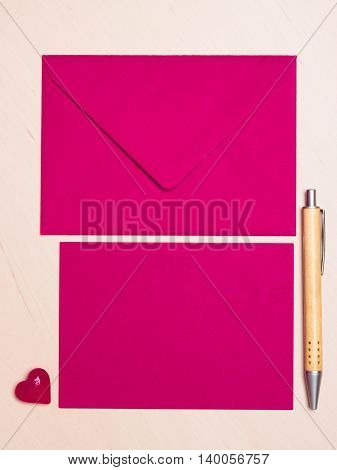 Pink blank sheet of paper with envelope and little heart pen on wooden surface. Background for valentines day or wedding card.