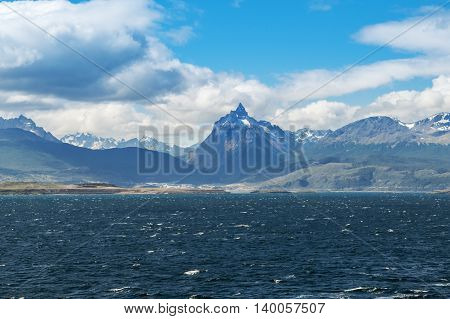 View of the Beagle channel with mountains on background. Beagle channe is a strait in Tierra del Fuego Archipelago on the extreme southern tip of South America partly in Chile and partly in Argentina.