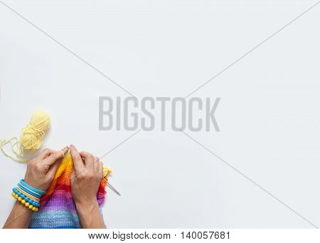 Woman knitting needles colored fabric. View from above. White background.