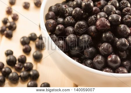 Bowl Full Of Aronia Spilled On Wooden Table