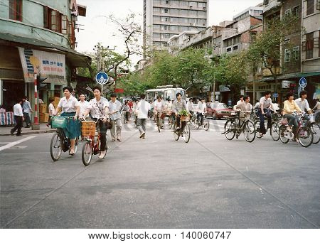 GUANGZHOU / CHINA - CIRCA 1987: People ride bicycles through the streets of Guangzhou.