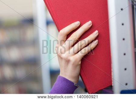 Woman taking a book in a library