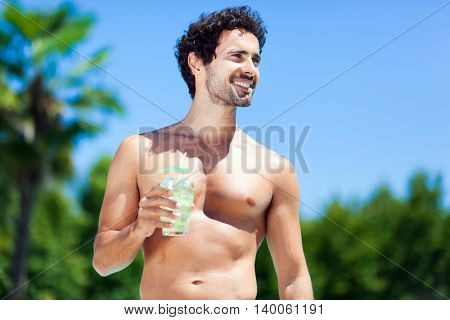 Handsome young man drinking a cocktail while relaxing in a swimming pool