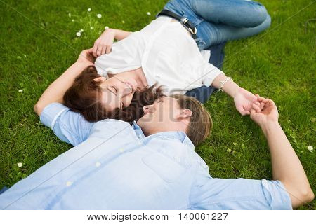 Couple relaxing and looking at each other on the grass
