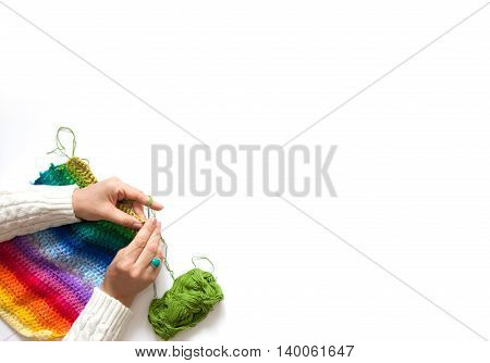 The Woman Knits A Hook Colored Fabric. View From Above.