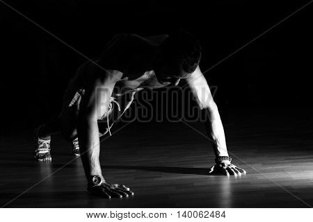 Man Making Burpees During Strength Training In Gym.