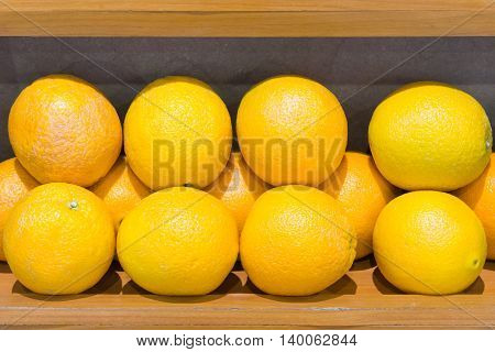 Fresh organic lemon which located on the wooden shelf of the local market.