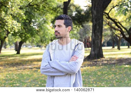 Portrait of young latin man thoughtful in a park. Outdoors.