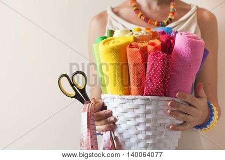 A Woman Holds Bright Colored Fabrics For Sewing And Scissors.