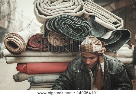Old Delhi Rajasthan India - February 15 2016 : A shot of a street carpet merchant pushing his cargo along the street in Old Delhi India.