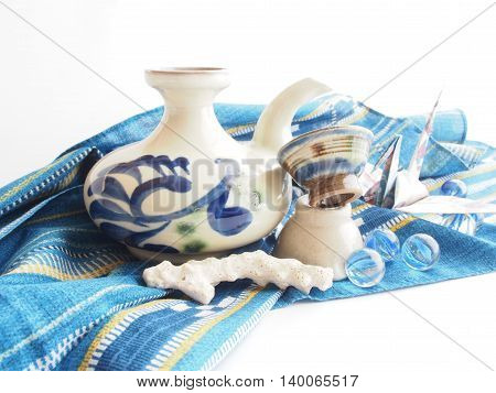 Okinawan traditional sake (millet brandy) cup and bottle, traditional cloth, blue marbles, white coral on white bright  background