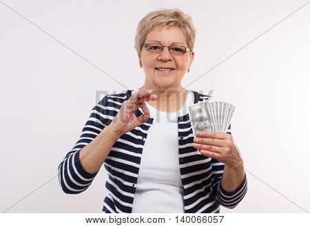 Happy Senior Female Holding Currencies Dollar And Showing Sign Ok, Concept Of Financial Security In