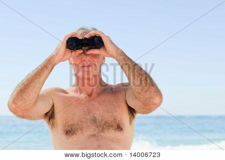 Senior Man Bird Watching At The Beach