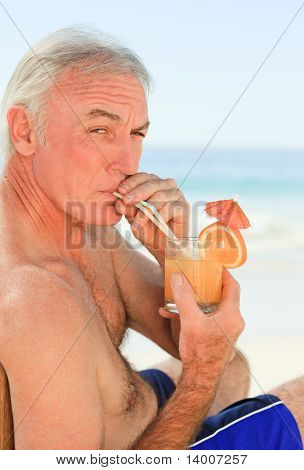Retired Man Drinking A Cocktail At The Beach