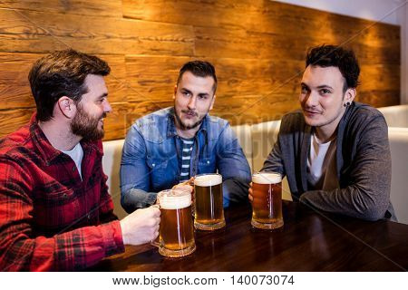 Young male friends enjoying beer at restaurant