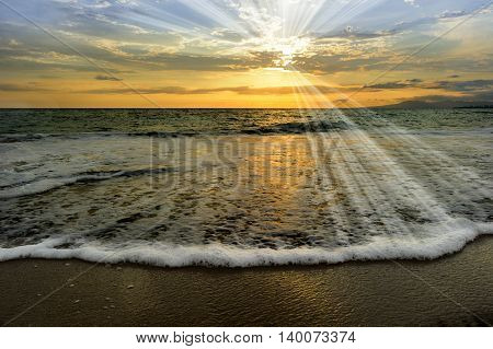 Ocean sunset rays is an ethereal ocean scenic with sun beams bursting forth from the setting sun as a gentle wave comes to shore.