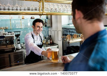 Bartender smiling while serving beer to male customer at restaurant