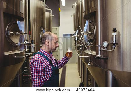 Side view of manufacturer looking at beer glass amidst machinery in brewery