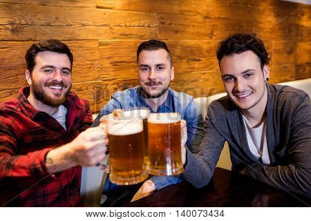 Portrait of male friends toasting beer at restaurant